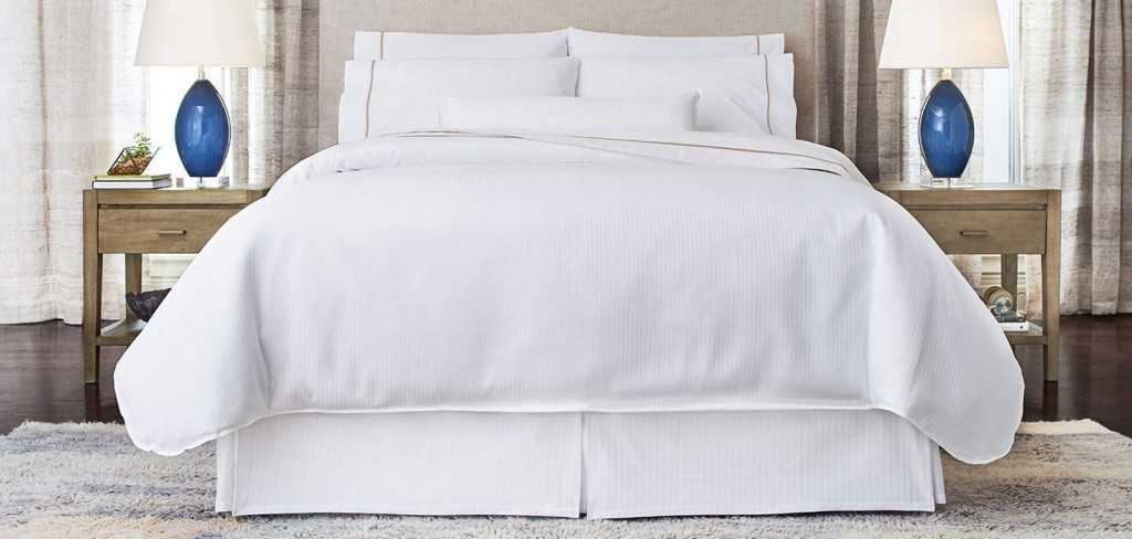 A white bed inside a Westin Hotel room